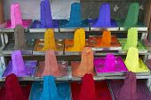 Piles of colored powder displayed on a market stall in the holy town of Pushkar India poster