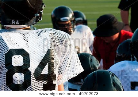American Football Team In Huddle
