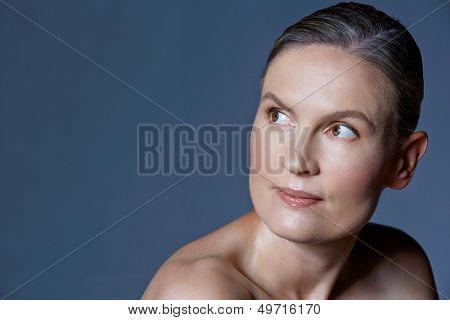beautiful forty year old woman with natural makeup and healthy skin texture on blue gray studio background with space for text