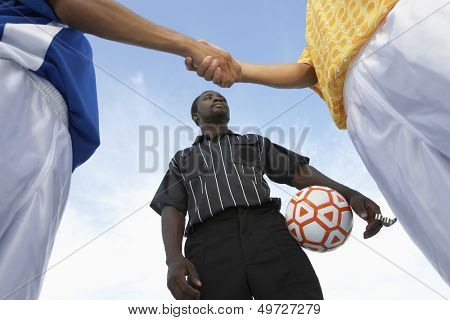Low angle view of referee with opponent team players shaking hand against sky