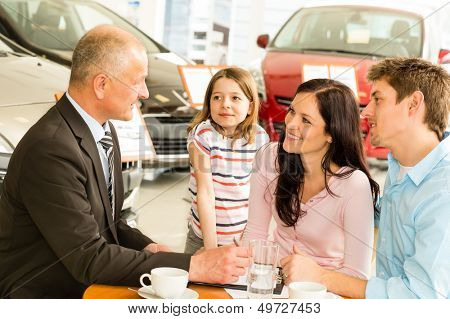 Car salesman and caucasian couple doing paperwork