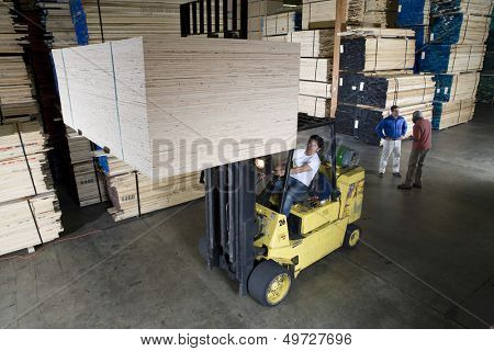 Manual worker operating a forklift truck in lumber industry