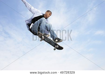 Low angle view of young man on skateboard in midair against cloudy sky