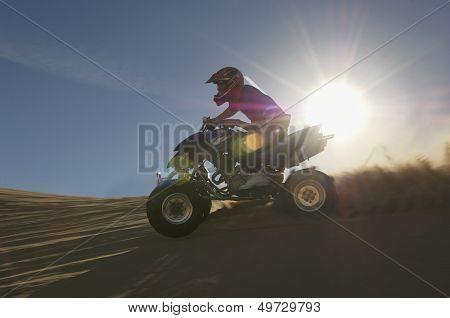 Young man riding quadbike in desert