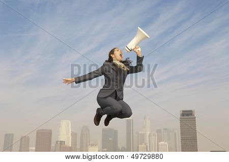 Full length of young businesswoman shouting into megaphone above city