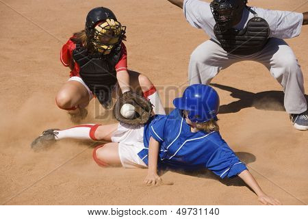 Jugador de softbol en plato de home, mientras que las reglas del árbitro seguras