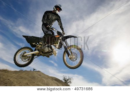 Low angle view of motocross racer in midair against cloudy sky poster