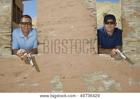 Two men holding hand guns at firing range, portrait