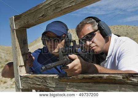 Instructor with man aiming machine gun at firing range