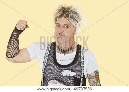 Portrait of senior male punk showing clenched fist over yellow background