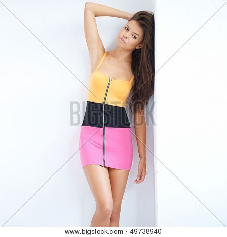 Trendy sexy young woman posing in a colourful miniskirt with her hand raised to her long brunette hair showing off her slender legs with copyspace
