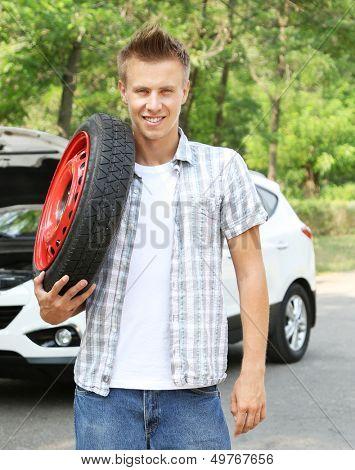 Man driver holding tire on shoulder