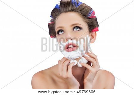 Thoughtful young model touching her face with shaving foam on white background