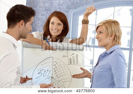 Happy businessteam discussing diagram on whiteboard in meeting room, smiling.