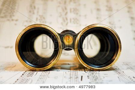 Antique Binoculars Over Classical Music Notes