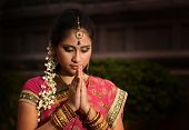 Portrait of beautiful young Indian woman in traditional sari dress praying in a hindu temple. poster