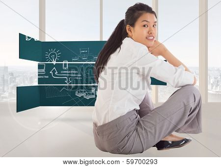 Businesswoman sitting cross legged smiling against bright white room with windows