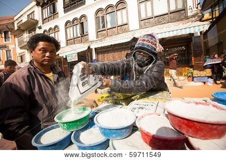 KHATMANDU, NEPAL - DEC 17, 2013: Unidentified man sell cement for donations for repairs near stupa Boudhanath during festive solemn Puja of H.H. Drubwang Padma Norbu Rinpoche's reincarnation's.