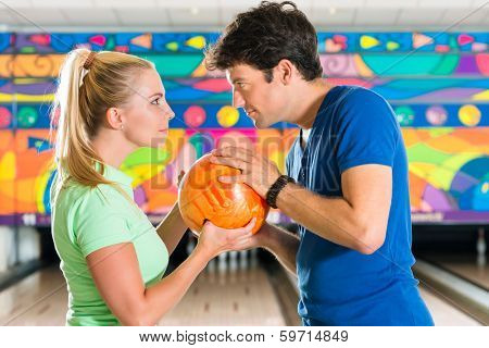 Young couple or friends, man and woman, playing bowling with a ball in front of the ten pin alley, they are a team