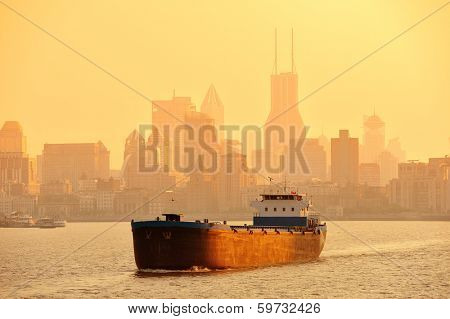 Boat in Huangpu River with Shanghai urban architecture at sunset