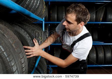 Young Mechanic Choosing Tire In Car Service