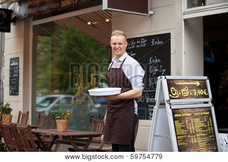 Young waiter with a tray