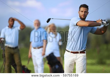 Handsome male golfer swinging golf club, following shot in the air. poster