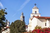 White Adobe Cross Steeples Bell Mission Red Bougainvillea Santa Barbara California. Founded in 1786 at the end of Father Junipero Serra life. poster