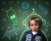 Imagination and dreams of a child, dressed as a space man in front of a blackboard with chalk drawings of space rocket and alien, concept for aspirations and daydreaming poster