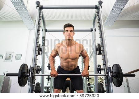 Low angle view of a shirtless muscular man lifting barbell in gym