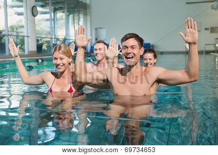 Fitness class doing aqua aerobics in swimming pool at the leisure centre