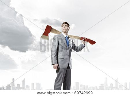 Young determined businessman with axe on shoulder