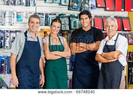 Portrait of confident salespeople standing arms crossed in hardware shop