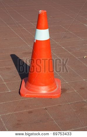 Red cone at roadworks on a tar road