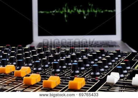 Analog studio sound mixer closeup with laptop and sound wave form in the background poster
