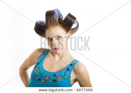 Young Beautiful Girl In Blue Shirt Is Getting Ready For Party With Curlers On Her Hair. Isolated On