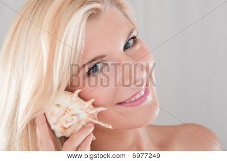Young beautiful woman with healthy pure skin and a sea shell