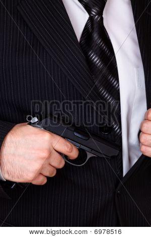 Man Drawing His Gun From Jacket Pocket