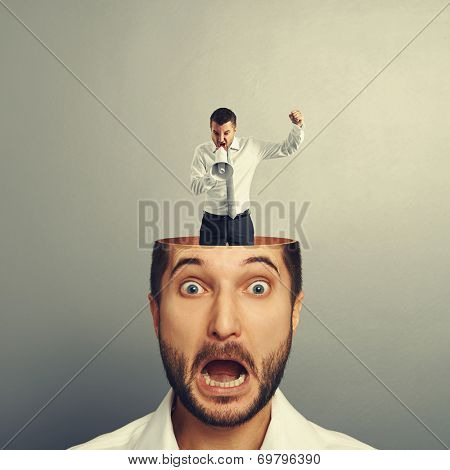 scared young man with screaming man in his head over grey background