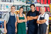 Portrait of confident salespeople standing arms crossed in hardware shop poster