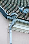 Old rain gutter with weathered tiled roof poster