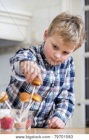 Boy putting cupcake pop in glass at kitchen counter