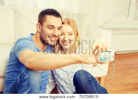 love, family, technology and happiness concept - smiling couple taking self portrait picture with digital camera at home