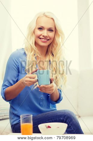 healthcare, food, home and happiness concept - smiling woman with cup of tea, glass of juice and bowl of muesli having breakfast poster
