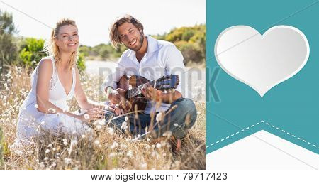 Handsome man serenading his girlfriend with guitar against heart label