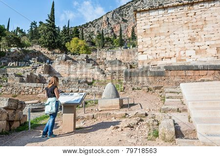Visitor reading a description table at ancient Temple of Apollo Delphi. poster