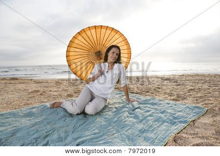 Hispanic Woman With Parasol On Beach Blanket
