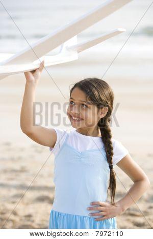 Cute Hispanic Girl Playing With Toy Plane On Beach