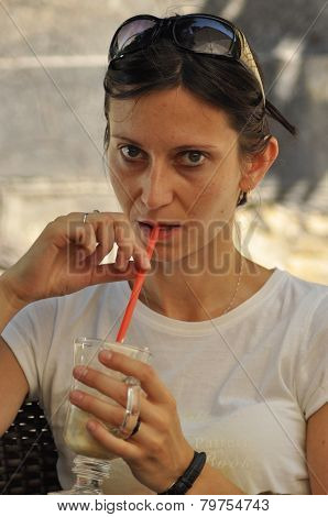 Woman Drinking A Drink. The Girl In The Bar On The Open Air