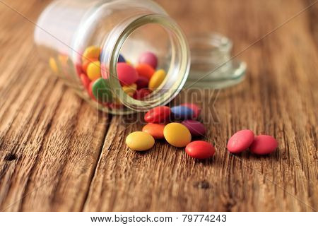 Color Smarties Around Glass Dose On Wooden Board